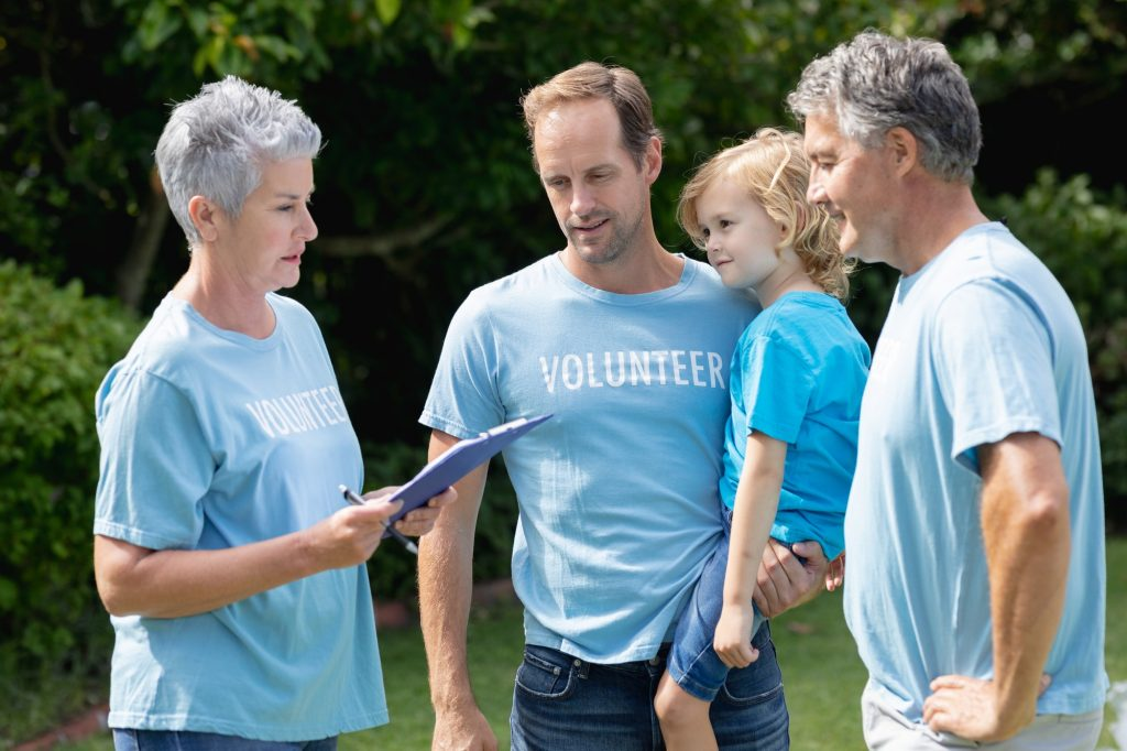 Caucasian senior couple with clipboard and father carrying son in volunteer shirts talking in field
