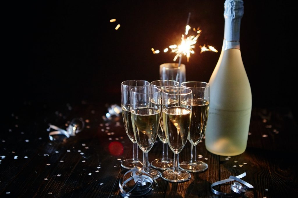 Party composition image. Glasses filled with champagne placed on black table